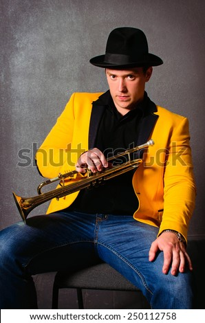 Handsome musician trumpet player with trumpet at studio. Jazz-band. Brutal young musician holding trumpet