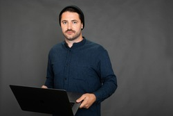 Handsome mustached unshaven hipster in knitted cap posing with laptop on gray studio backdrop copy space. Gray office routine, tiresome monotonous work, office sadness, lack of career prospects