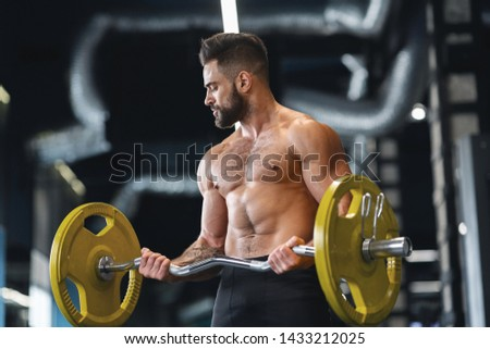 Handsome naked weightlifter lifting heavy barbell in gym, free space