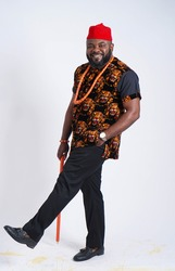 Handsome Nigerian man dressed in Igbo traditional attire and walking stick
