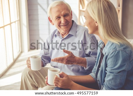 Handsome old man and beautiful young girl are  drinking tea, talking and smiling while sitting on couch at home