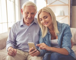 Handsome old man and beautiful young girl are using a smartphone, talking and smiling while sitting on couch at home