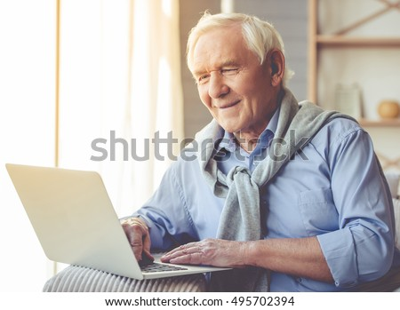 Handsome old man dressed in smart casual style is using a laptop and smiling while sitting on couch at home #495702394