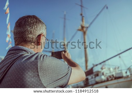 Handsome old man on vacation at summertime next to sea in port with boats using mobile phone and taking pictures of big sealing yacht