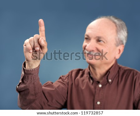 handsome old man pointing up on blue background. Focus on hand