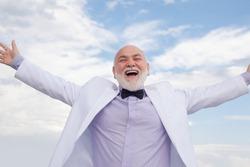 Handsome oldfashion winner senior old mature man. Vintage success male in white suit having fun
