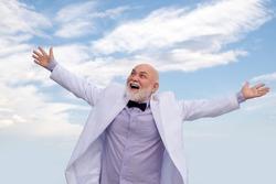 Handsome oldfashion winner senior old mature man. Vintage success male in white suit having fun.