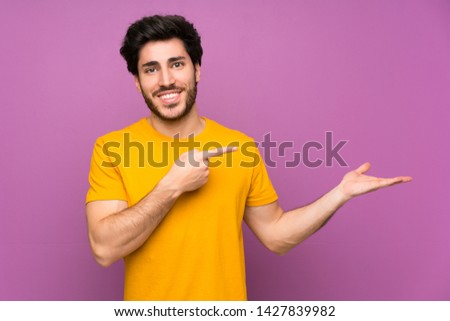Handsome over isolated purple wall holding copyspace imaginary on the palm to insert an ad
