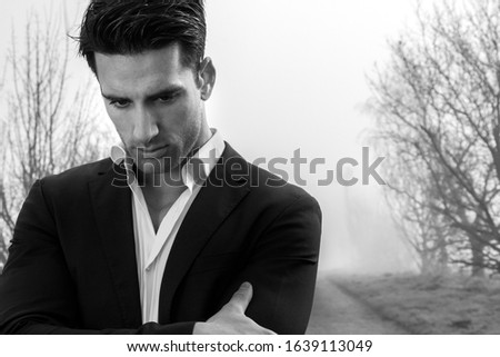 Handsome pensive male wearing suit and bowtie standing on a lonely foggy road with his arms folded