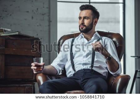 Handsome pensive man is holding a glass of whiskey and looking away while sitting in leather armchair indoors #1058841710