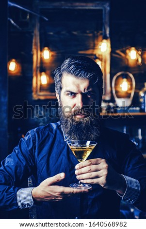 Handsome pensive man is holding a glass of whiskey. Drink party