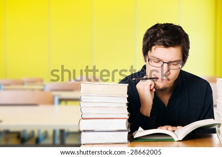 Handsome pensive young man studying on a stack of books on desk at school