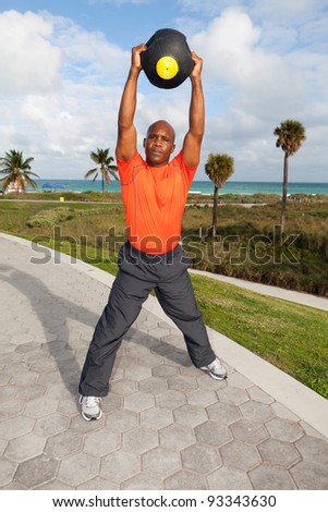 Handsome personal trainer exercising in a popular South Beach park in Miami.