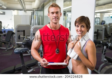 Handsome personal trainer with his client smiling at camera at the gym