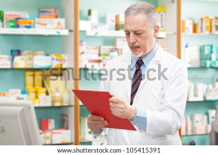 Handsome pharmacist reading a prescription