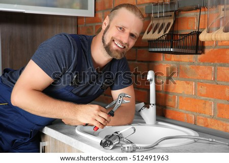 Handsome plumber replacing faucet in kitchen, close up view #512491963