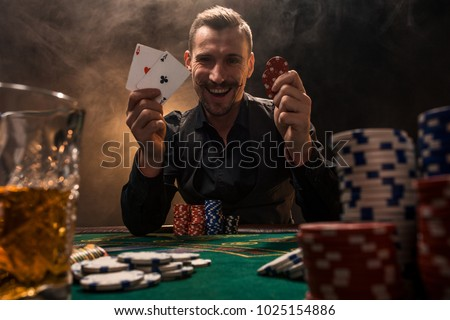 Handsome poker player with two aces in his hands and chips sitting at poker table in a dark room full of cigarette smoke.