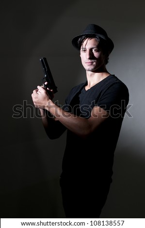 Handsome police private detective man on the job with a gun