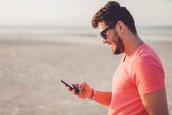 handsome portrait man using smartphone, happy face, sunglasses, beard, beach, sea, travel, internet, Outdoor portrait, hipster style, holding phone in hand, answer texts message. beard man, instagram