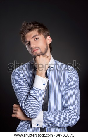 Handsome positive young business man standing and thinking