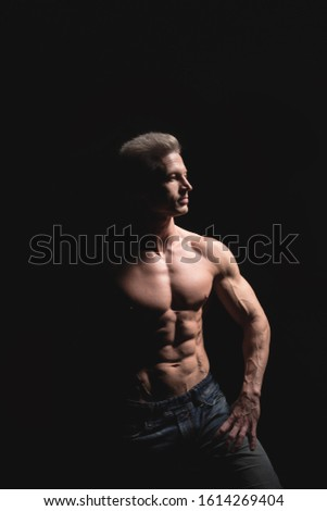 Handsome power athletic man in dramatic light. Strong bodybuilder with perfect shoulders, biceps, triceps, back, delta and chest. Strength and motivation