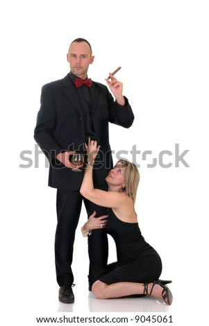 Handsome pre middle aged gigolo in formal suit with bow tie, woman at his feet, white background,  studio shot.