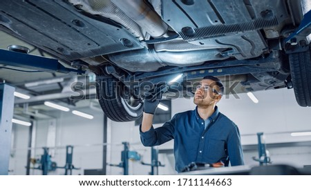 Handsome Professional Car Mechanic is Investigating Rust Under a Vehicle on a Lift in Service. Repairman is Using a LED lamp and Walks Towards. Specialist is Wearing Safety Glasses. Modern Workshop. Photo stock ©