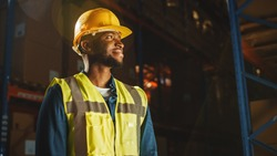 Handsome Professional Worker Wearing Safety Vest and Hard Hat Charmingly Smiling and Looks Into the Distance. In the Background Big Warehouse with Shelves full of Delivery Goods. Medium Portrait