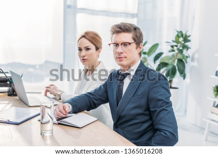 handsome recruiter in glasses sitting with attractive coworker in office