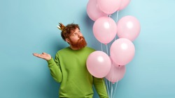Handsome redhead birthday man wears festive crown and green sweater, focused upwards, carries balloons with helium, raises palm against copy space, comes on party. Holiday and celebration concept