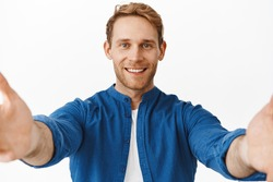 Handsome redhead man smiling, talking on video call conference and adjusting camera with stretch out hands, holding device while taking selfie, standing over white background