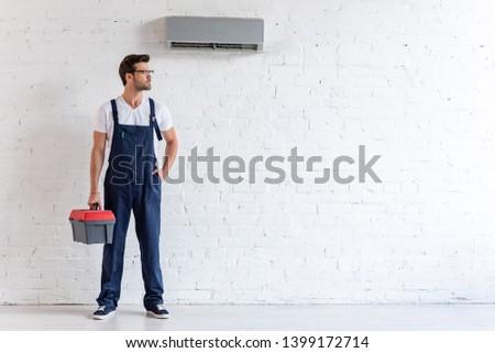 handsome repairman in uniform standing under conditioner and looking away #1399172714