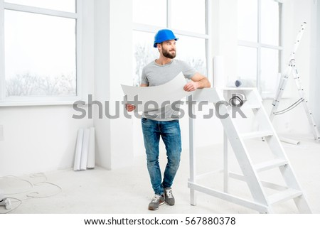 Handsome repairman or builder in helmet working with drawings on renovation of apartment interior