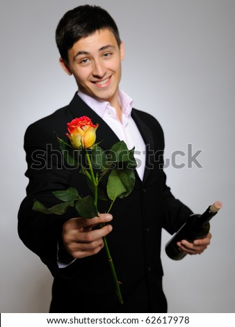 Handsome romantic young man holding rose flower and vine bottle  prepared for a date. gray background