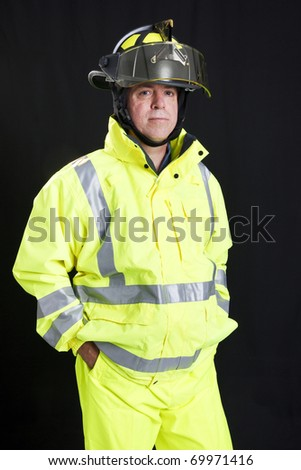 Handsome, rugged firefighter photographed on a black background.