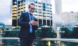Handsome satisfied gray haired bearded businessman in black suit and blue tie in glasses texting on smartphone by glass fence on blurred background in New York