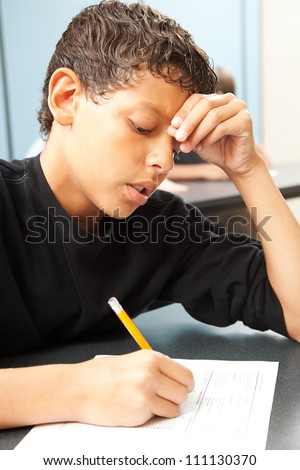 Handsome school boy struggling to finish a test in class.