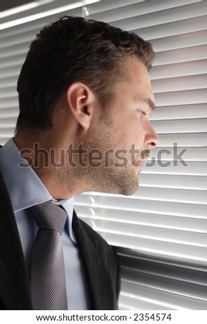 Handsome secret  business man looking through window blinds