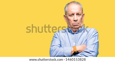 Handsome senior businesss man wearing elegant shirt skeptic and nervous, disapproving expression on face with crossed arms. Negative person. Сток-фото ©