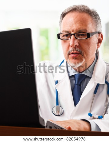 Handsome senior doctor using a laptop computer