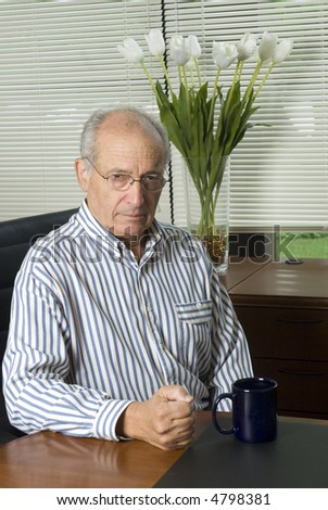 handsome senior executive in office expressive face - stock photo