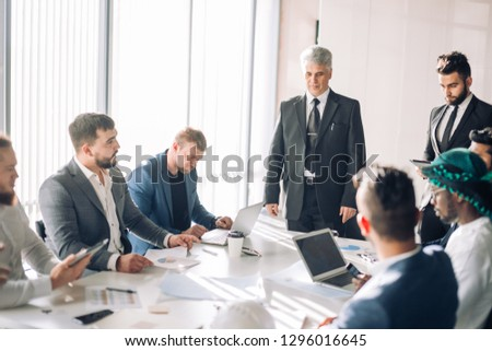Handsome Senior grey-haired caucasian Executive leading the meeting of international partners in boardroom, having positive mood and introducing the new board member to his colleagues