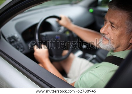handsome senior man driving a car (shallow DOF; sharp focus on the eye)
