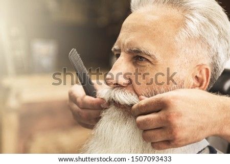 Handsome senior man getting styling and trimming of his beard in the barbershop