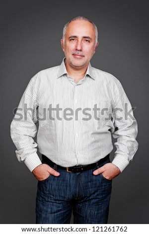 handsome senior man looking at camera and smiling. studio shot over grey background