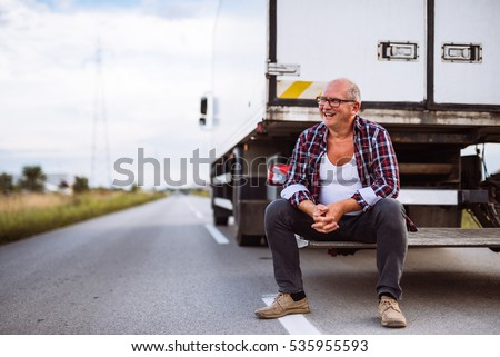 Handsome senior man sitting on the back side of his truck.