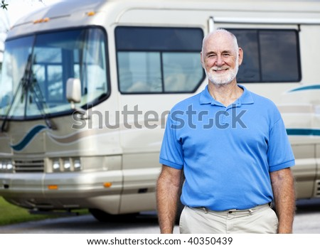 Handsome senior man standing in front of his luxury motor home.