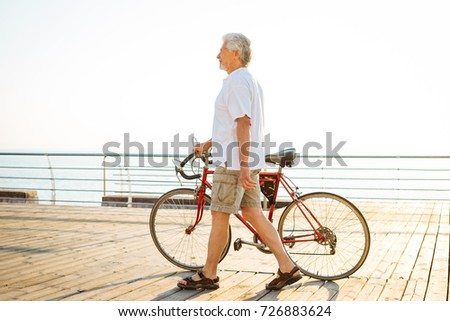 Handsome senior man walking with bike on seafront #726883624
