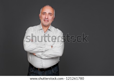 handsome senior man with folded hands looking at camera and smiling. studio shot over grey background