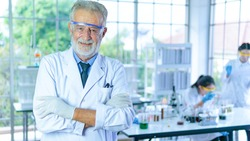 Handsome senior scientist man wearing white dress coat stand in front interior laboratory background smiling positive. Successful face and feeling expression.